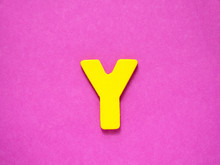 Capital Letter Y. Yellow Letter Y From Wood On Purple Background.