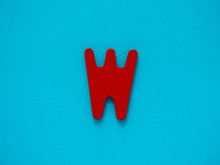 Capital Letter W. Red Letter W From Wood On Blue Background.
