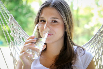 Młoda kobieta pije wodę ze szklanki