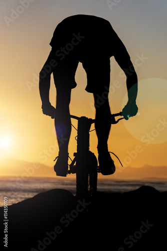plakat CYCLIST RIDING OVER ROACKS INTO A SOUTH AFRICAN SUNSET