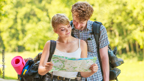 fototapeta na lodówkę Hiking backpacking couple reading map on trip.