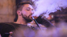 Handsome Man Smokes Hookah In ...