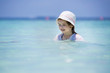 Cute little girl in bathing suit playing in the clear ocean on the tropical resort beach with white sand, azure blue sea and coconut palms. Paradise Landscape background. Happy and excited child.