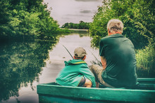 Grandfather And Boy Fishing To...
