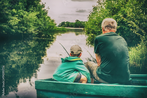 Cadres-photo bureau Peche grandfather and boy fishing together. HDR. boy and an old man sitting in a boat with a fishing rod. view from the back