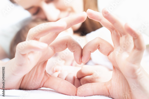 obraz dibond Happy mother and baby. Heart symbol by hands. Family care