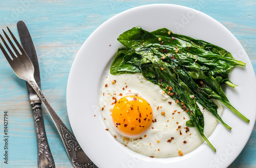 Poster Gebakken Eieren Fried egg with spinach on the wooden table