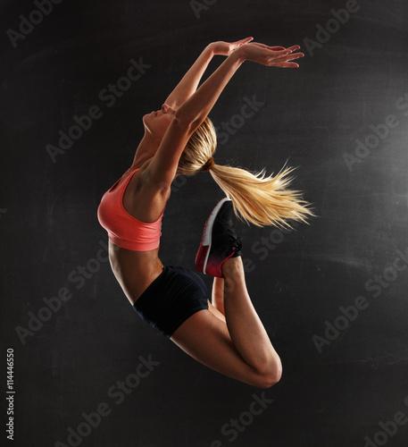 szczupla-blondynka-wyskakujaca-w-trakcie-cwiczen