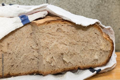 fototapeta na szkło Crusty french pain de campagne wrapped with a white napkin
