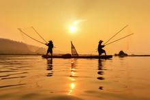 Fishermen Throwing Net In Mekong River During Sunset