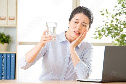 Fotografia  Young asian business woman with tooth sensitivity