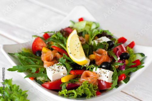 obraz PCV Salmon salad traditional serving with lemon on white wooden background. Top view on white bowl with smoked salmon salad, pepper, brie, olives, lettuce, decorated with slice of lemon.