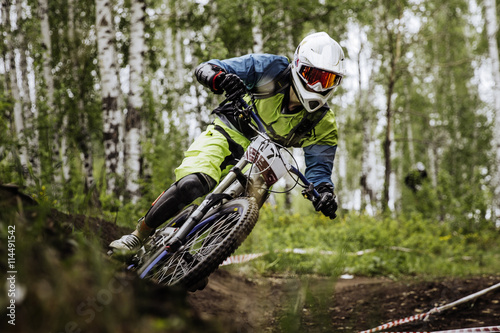 closeup man athlete mountain biking around sharp turn in forest during competiti Fototapeta
