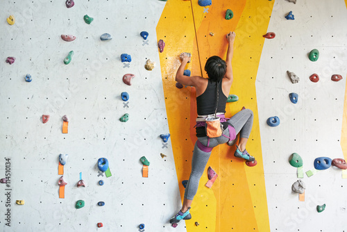 Fototapeta Back view of sportswoman climbing in the gym obraz