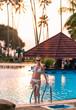 Pretty woman in white bikini posing by swimming pool