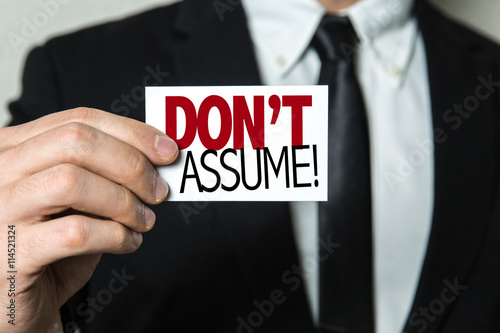 Fotografie, Obraz  Business man holding a card with the text: Don't Assume