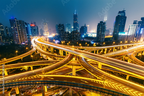 View over the famous highway intersection in Shanghai, China, with illuminated highways and modern architecture. Shanghai skyline by night.