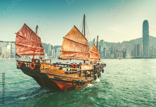 Spoed Foto op Canvas Hong-Kong Scenic view over Hong-kong skyscprapers and a junkboat sailing. Iconic landmark of Hong-Kong.