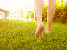 Close Up Female Legs Walking On The Grass.