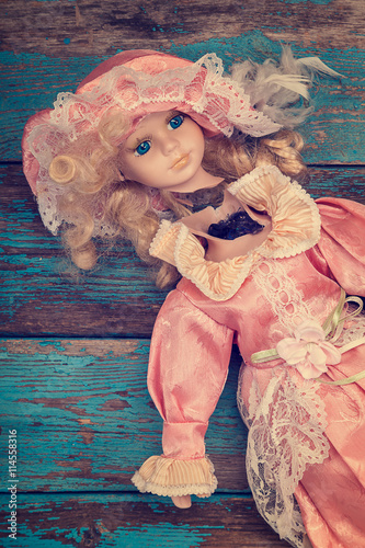 Photo sur Toile Carnaval Broken doll on a wooden floor.