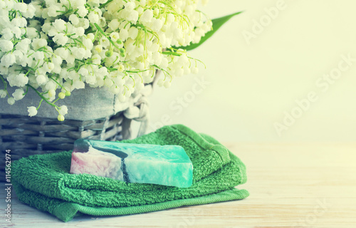 Stickers pour porte Muguet de mai Natural soap of handwork, towel, and spring flowers of a lily of the valley in a wattled basket on a wooden surface