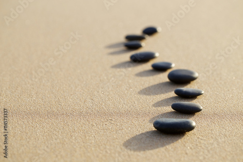 set of hot stone on white sand calm beach in backbone shape. sel