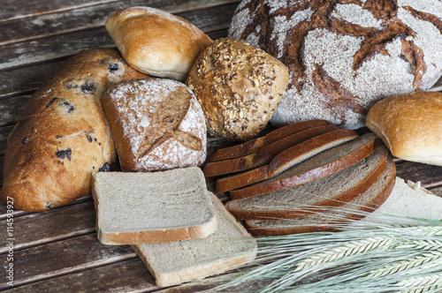 fototapeta na drzwi i meble Verschiedene Brotsorten auf einem Holztisch / Verschiedene Brotsorten mit Getreideaehren auf einem Holztisch.