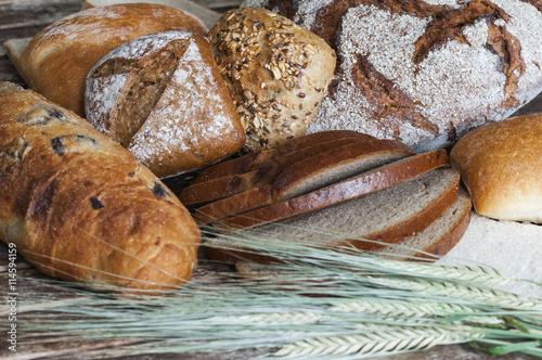 fototapeta na lodówkę Verschiedene Brotsorten auf einem Holztisch / Verschiedene Brotsorten mit Getreideaehren auf einem Holztisch.