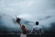 Wedding. Mountains . Bride's Bouquet . Artwork. Grain. The Guy And The Girl In A Dress Standing Against A Background Of High Mountains And Holding Hands, She Is Holding A Wedding Bouquet