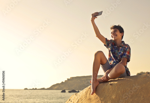 obraz lub plakat Young boy doing a selfie at the beach
