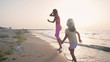 Young mother with her little daugter running on the beach near the water, slowmo