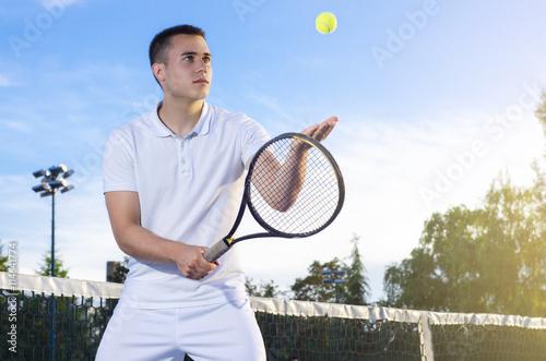 Jeune joueur de tennis lancer la balle en l'air, au service, mise au point s Poster