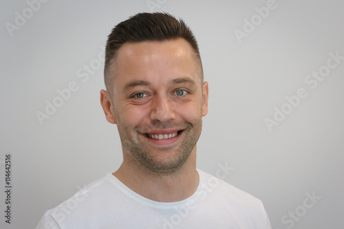 obraz dibond Portrait of young handsome man in white T-shirt
