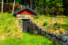 Root Cellar Close To The Forest With Stone Boulders Leading Up To The Entrance.