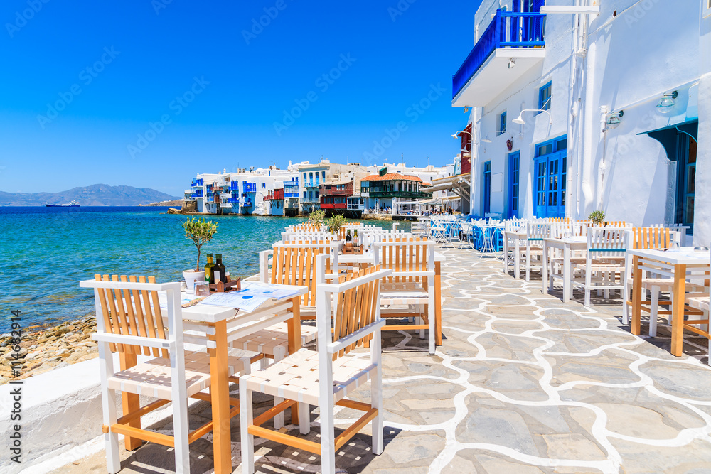 Fototapeta Chairs with tables in typical Greek tavern in Little Venice part of Mykonos town, Mykonos island, Greece