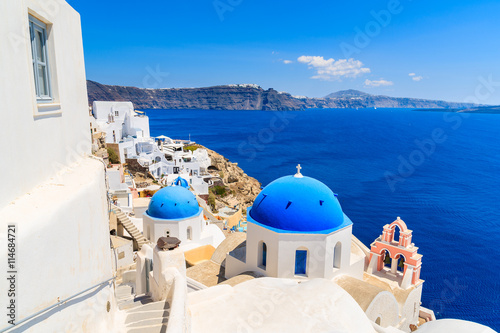 Papiers peints Santorini Famous blue dome of a church in Oia village and view of blue sea with caldera on Santorini island, Greece