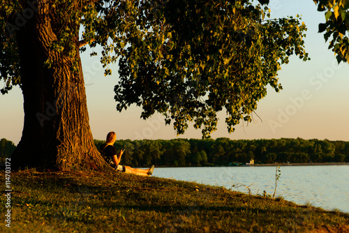 Fototapety, obrazy: young blond woman sitting in a large tree in the background of t
