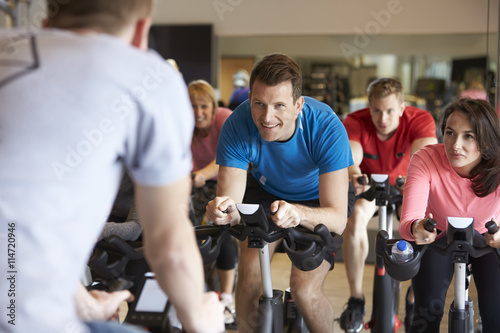 Photo Instructor in foreground with spinning class at a gym