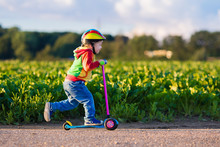 Little Boy Riding A Colorful Scooter