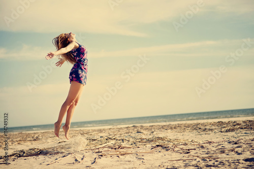 Fotografia  Beautiful young woman jumping at the beach