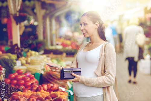 mata magnetyczna pregnant woman with wallet buying food at market