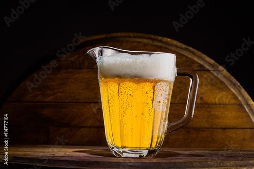Fototapeta Pitcher of beer on wooden background obraz