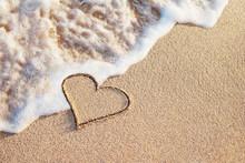 Heart Symbol Handwritten On Sandy Beach With Soft Ocean Wave