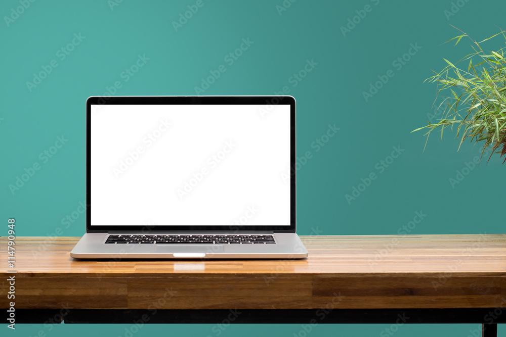 Fototapeta laptop on wooden desk with green wall background