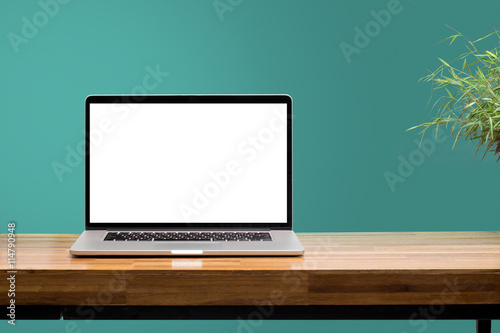 Fototapeta laptop on wooden desk with green wall background obraz