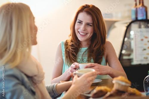 Fényképezés  Happy beautiful woman with friend at cafe
