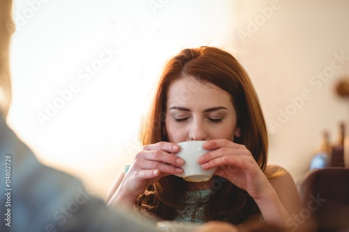 Fényképezés  Beautiful woman sipping coffee with friend at cafe