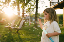 Young Girl Playing With Bubble Wand