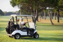 Mature Golfer Friends Sitting In Golf Buggy