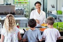 Cheerful Woman Serving Food To Schoolchildren